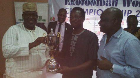 Seyi Akinwunmi (L) presents trophy to Wale Joseph (c) Chairman Organising Committee